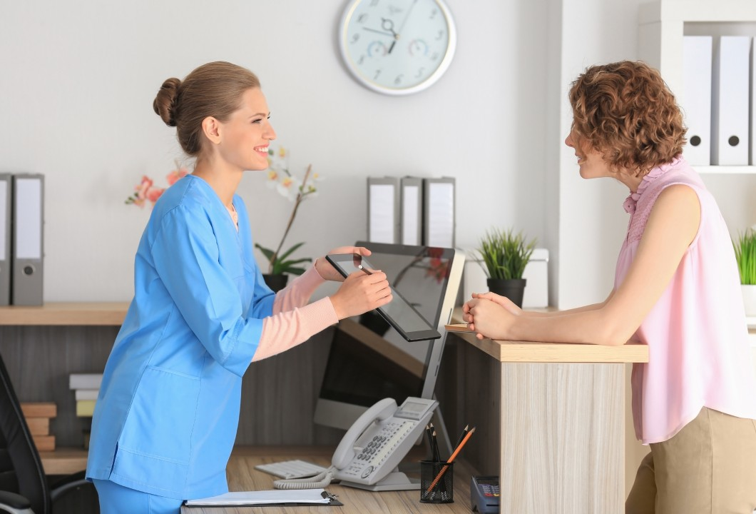 Medical-receptionist-with-patient